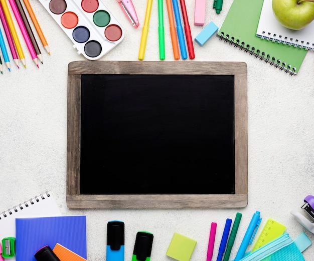Vista dall'alto di nuovo a materiale scolastico con lavagna e matite colorate