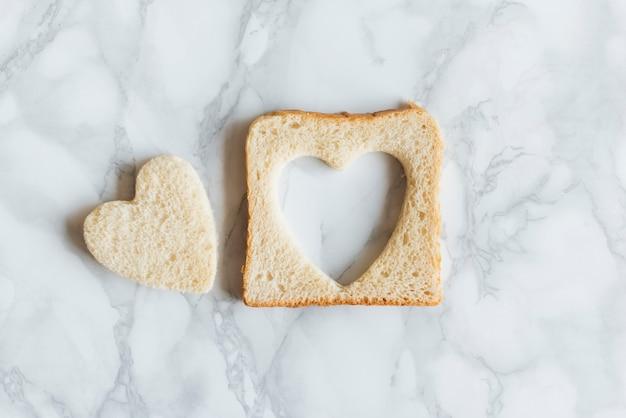 Vista dall'alto di pane con cuore su sfondo di mabrle