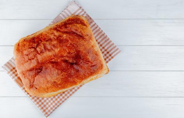 Vista dall'alto di pane fatto in casa sul panno plaid e sullo sfondo in legno con spazio di copia