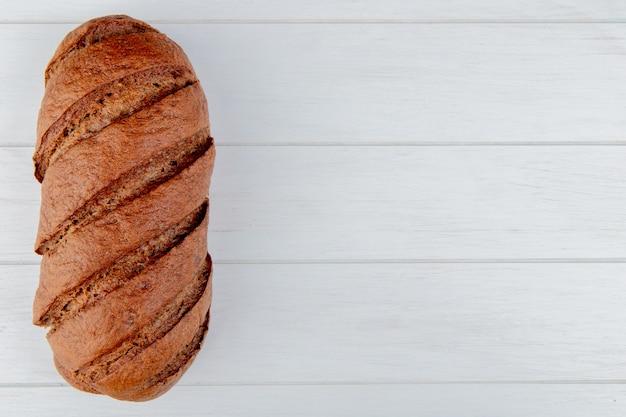 Vista dall'alto di pane nero su fondo in legno con spazio di copia