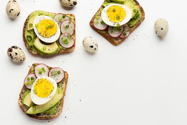 Vista dall'alto di panini con uova e avocado con spazio di copia