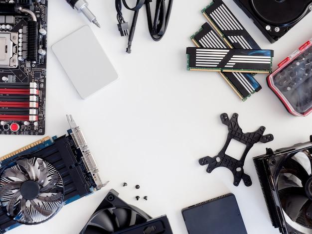 Vista dall'alto di parti di computer con hard disk, unità a stato solido, ram, cpu, scheda grafica e scheda madre su sfondo bianco da tavolo.