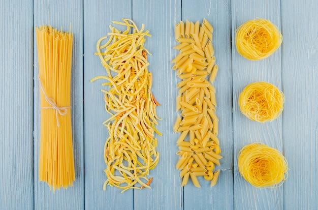 Vista dall'alto di pasta cruda di diverse forme e spaghetti su legno
