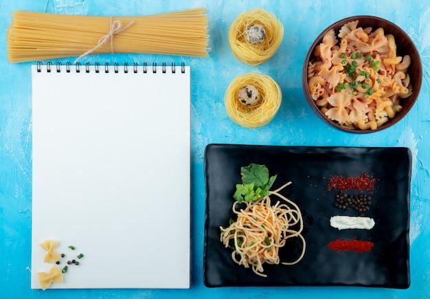 Vista dall'alto di pasta cruda di diverse forme e tipi come spaghetti nido di pasta gialla con uova di quaglia e pasta di farfalle cotte in una ciotola e pasta di spaghetti su un piatto nero con sket