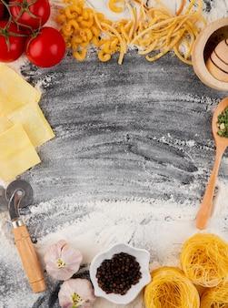 Vista dall'alto di pasta cruda di diverse forme e tipi di pomodori freschi e aglio su sfondo nero con farina con spazio di copia