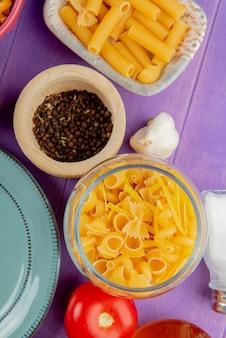 Vista dall'alto di pasta in barattolo con pepe nero e pomodori