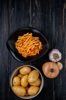 Vista dall'alto di patate in ciotole fritte e crude intere con sale e aglio su legno
