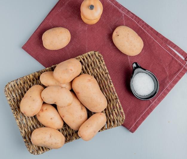 Vista dall'alto di patate nel piatto e sul panno bordo con sale sulla superficie blu