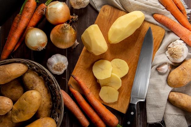 Vista dall'alto di patate sbucciate con aglio e cipolla
