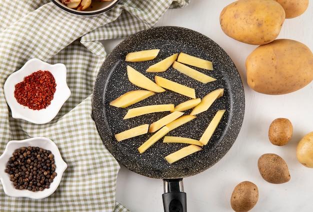 Vista dall'alto di patate tritate in padella secche scaglie di peperoncino e pepe nero sulla tovaglia