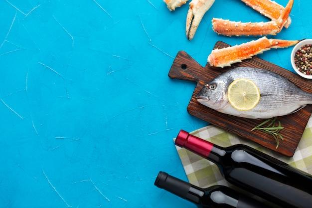 Vista dall'alto di pesce fresco con vino sul tavolo