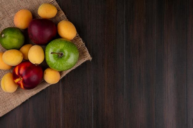 Vista dall'alto di pesche con albicocche e una mela verde su un tovagliolo beige su una superficie di legno