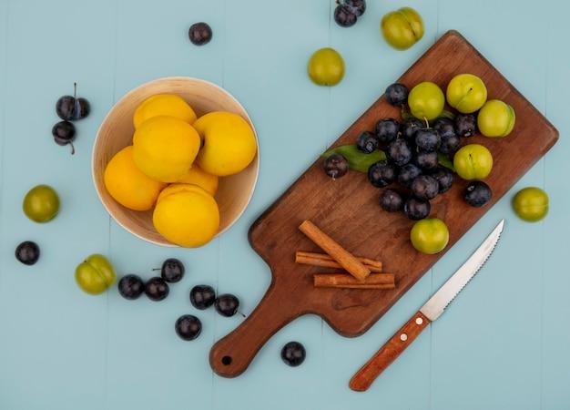 Vista dall'alto di pesche gialle fresche su una ciotola con prugnole su una tavola di cucina in legno con prugne ciliegia verdi con coltello su sfondo blu