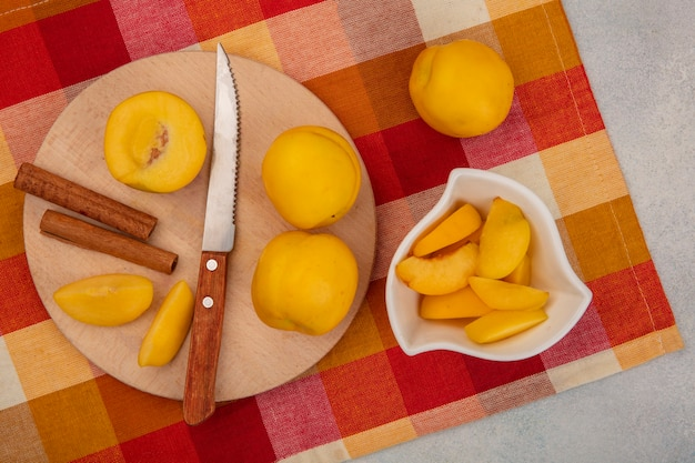 Vista dall'alto di pesche gialle fresche su una tavola da cucina in legno con coltello con bastoncini di cannella con fette tritate di pesche gialle su una ciotola bianca su una tovaglia a quadretti su sfondo bianco