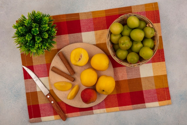 Vista dall'alto di pesche gialle su una tavola da cucina in legno con bastoncini di cannella con coltello con prugne ciliegia verde su un secchio su una tovaglia a quadretti su sfondo bianco