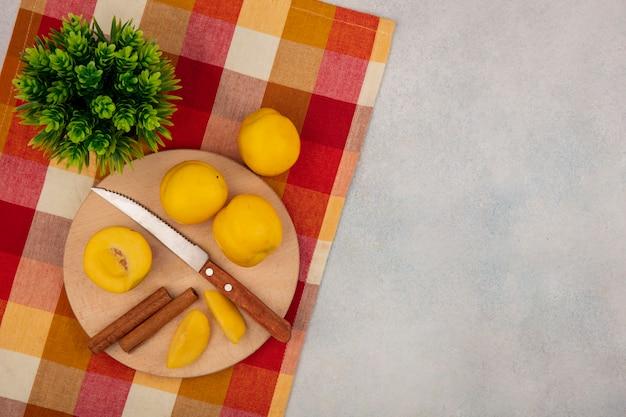 Vista dall'alto di pesche gialle su una tavola da cucina in legno con coltello con bastoncini di cannella su una tovaglia a quadri su uno sfondo bianco con spazio di copia