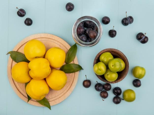 Vista dall'alto di pesche gialle su una tavola da cucina in legno con prugne ciliegia verdi su una ciotola di legno su sfondo blu