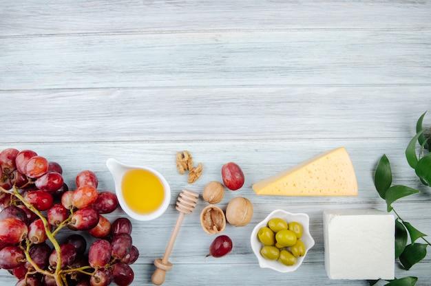 Vista dall'alto di pezzi di formaggio con miele, uva fresca, olive in salamoia e noci sul tavolo di legno grigio con spazio di copia