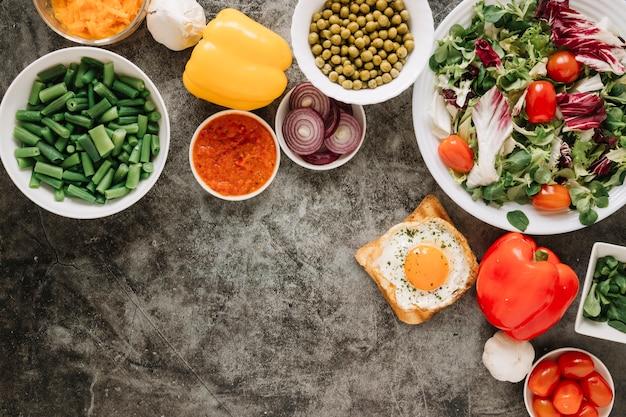 Vista dall'alto di piatti con insalata e uovo fritto su pane tostato