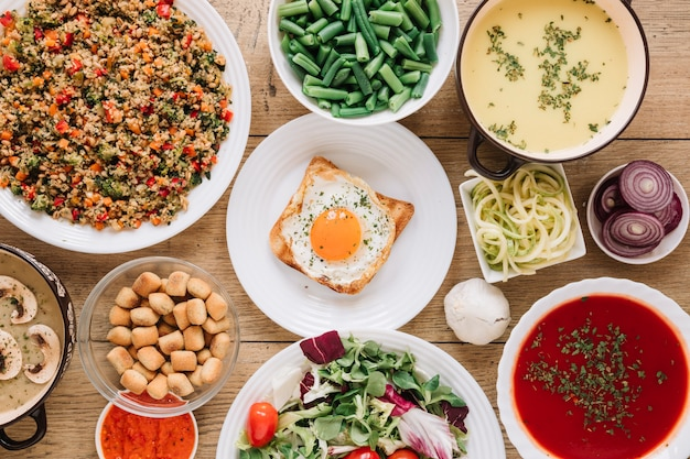 Vista dall'alto di piatti con uovo fritto e zuppa di pomodoro