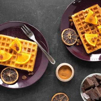 Vista dall'alto di piatti con waffle e agrumi