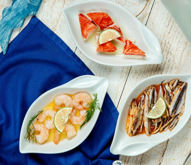 Vista dall'alto di piatti di pesce con contorno di polpa di granchio e acciuga