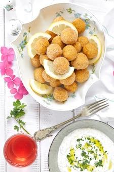 Vista dall'alto di piatto con falafel e salsa di salsa con yogurt, tahine e prezzemolo.