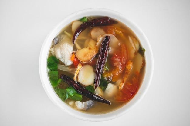 Vista dall'alto di piccante e piccante thai tom yum kung con ingredienti ed erbe.
