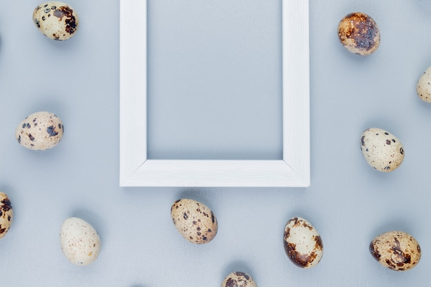 Vista dall'alto di piccole uova di quaglia con conchiglie color crema su uno sfondo bianco con spazio di copia