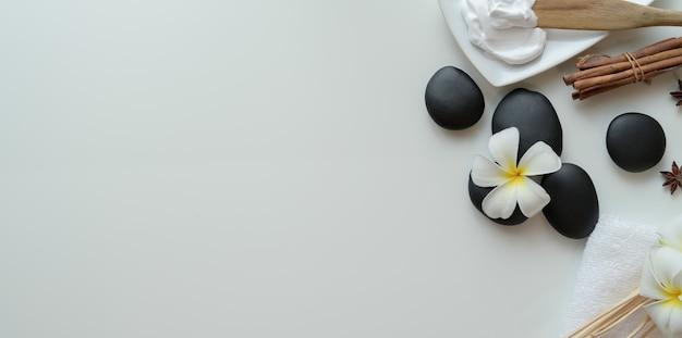 Vista dall'alto di pietre nere e accessori per massaggi su bianco