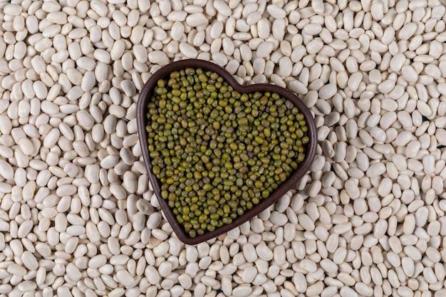 Vista dall'alto di piselli in una ciotola a forma di cuore con fagioli bianchi