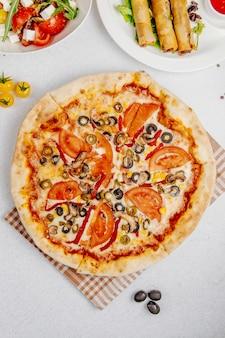 Vista dall'alto di pizza con pomodori funghi e olive
