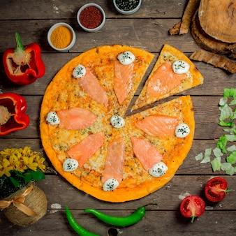 Vista dall'alto di pizza con salmone e formaggio philadelphia