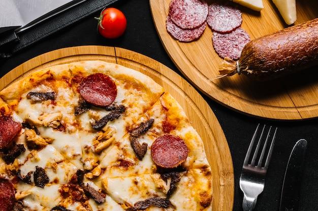 Vista dall'alto di pizza di carne mista con salame piccante, pollo e manzo