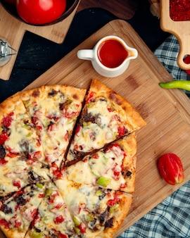 Vista dall'alto di pizza italiana con carne, pepe e pomodoro