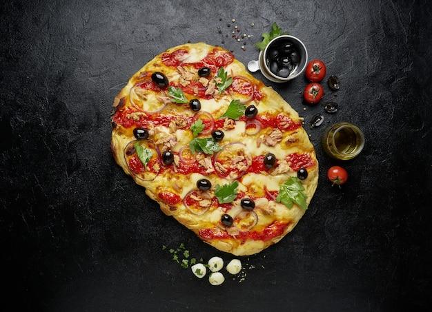 Vista dall'alto di pizza quadrata o pinsa con tonno su sfondo nero ardesia