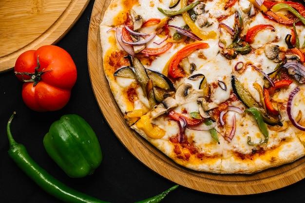 Vista dall'alto di pizza vegetariana con melanzane, peperoni, cipolla rossa, pomodoro e funghi