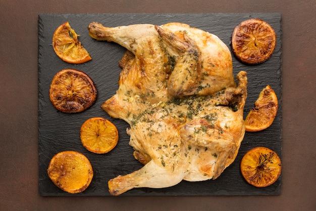 Vista dall'alto di pollo al forno con fette d'arancia