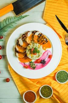 Vista dall'alto di pollo alla griglia con riso mescolato con piselli e cornon un piatto bianco
