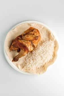 Vista dall'alto di pollo alla griglia intero e riso servito su focaccia