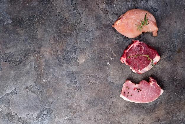 Vista dall'alto di pollo crudo, manzo e braciola di maiale insieme. proteine magre.