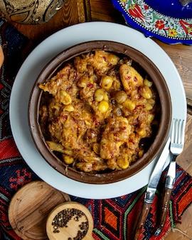 Vista dall'alto di pollo in umido con castagne e cipolla in una ciotola di argilla su un tavolo di legno