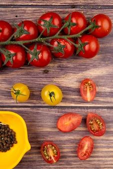 Vista dall'alto di pomodori con semi di pepe nero su superficie di legno