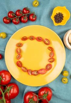 Vista dall'alto di pomodori gialli e rossi con semi di pepe nero e tagliare i pomodori nel piatto sul tavolo di stoffa blu