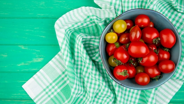 Vista dall'alto di pomodori in una ciotola sul panno sul lato destro e superficie verde