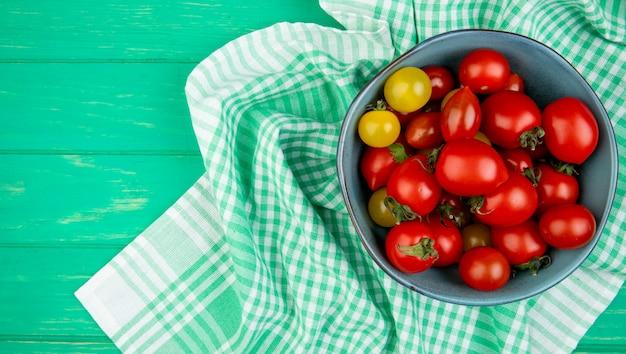 Vista dall'alto di pomodori in una ciotola sul panno sul lato destro e verde