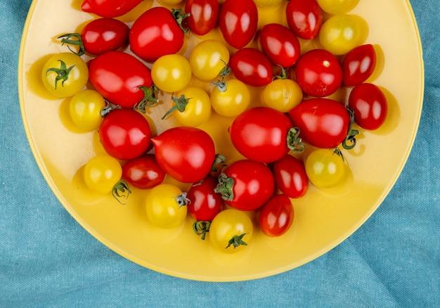 Vista dall'alto di pomodori nel piatto sulla superficie del panno blu