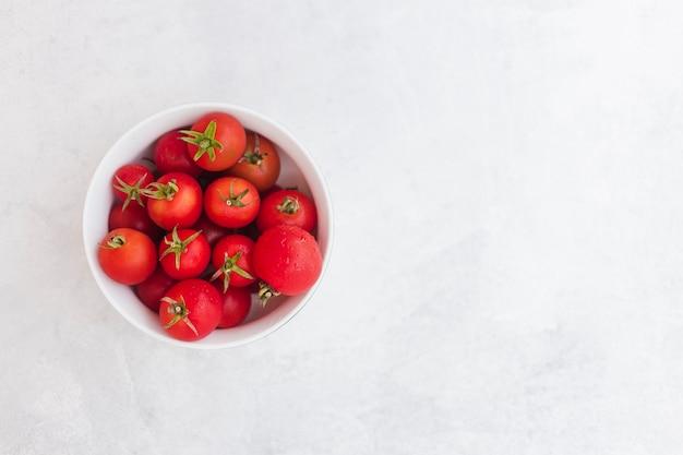 Vista dall'alto di pomodori rossi nella ciotola bianca su sfondo bianco