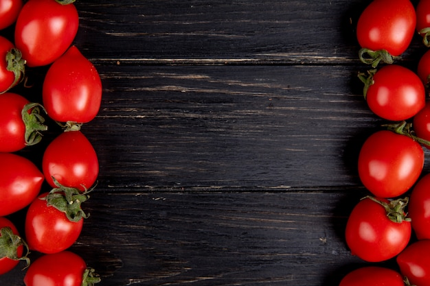 Vista dall'alto di pomodori sui lati sinistro e destro e legno con spazio di copia