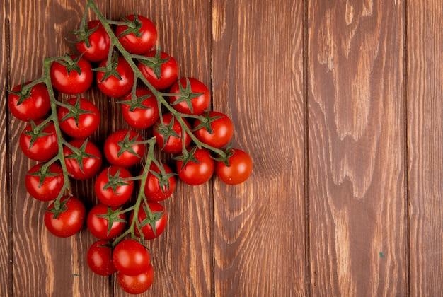 Vista dall'alto di pomodori sul lato sinistro e legno con spazio di copia